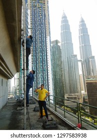 Kuala Lumpur,Malaysia - January, 2019 : Man working at height with Kuala Lumpur City View in the background. - image