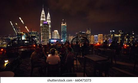 KUALA LUMPUR/MALAYSIA - MARCH 13, 2017: People sitting at the Heli Lounge Bar on the helipad of Menara KH tower with great night view of Kuala Lumpur and Petronas Twin Towers