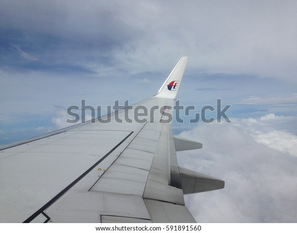 Kuala Lumpur,Malaysia-Febuary 15,2017 : Aerial view of the cloudy,blue sky and airplane wing as seen through window of an aircraft Malaysia Airlines.