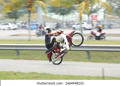 Kuala Terengganu, Malaysia- 27 July 2019. A man wheelie his motorbike at main road with some skill. it's dangerous for road user and himself. police should take action and give a punishment.
