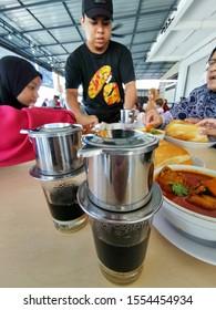 KUALA TERENGGANU, MALAYSIA-NOVEMBER 9, 2019 :  People eat breakfast consists of Vietnam drip coffee, chicken curries and baguette bread in Terengganu, Malaysia.