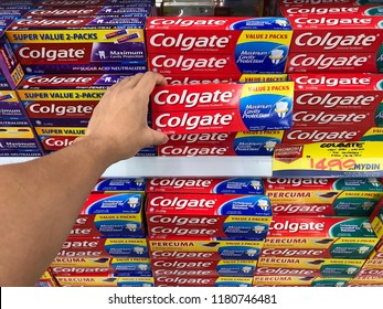 KUALA TERRNGGANU, MALAYSIA - September 1, 2018 :  Different types of colgate toothpaste assorted on supermarket shelves for sale with hand picking up item.