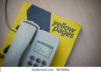 KUANTAN, MALAYSIA - December 23, 2017 : Yellow pages phone book with telephone isolated on desk.