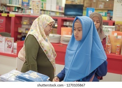 Kuantan, Malaysia - December 27th, 2018 : Young girl and mom in supermarket. Young girl try wearing school uniform  by mom for come back go to school in new semester. Back to school concept.