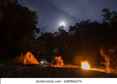KUANTAN, MALAYSIA - FEBRUARY 10TH 2020 : Men fire camping at night in the jungle and moon rise at background in Kuantan, Malaysia.