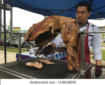 KUANTAN, MALAYSIA- JULY 18, 2018: A chef preparing roasted lamb or mutton on spit for academic staff in IIUM