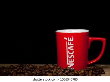 KUANTAN, MALAYSIA - MARCH 28, 2018 : Nescafe mug with coffee bean isolated on black background. Nescafe is a product from Nestle