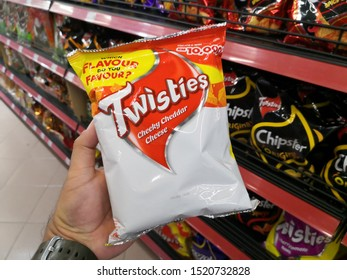KUANTAN, MALAYSIA - SEPT 24,2019: Hand holding TWISTIES corn snack on a supermarket shelf. Twisties are a type of cheese curl, corn-based snack food product.