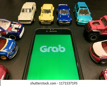KUANTAN, MALAYSIA- SEPTEMBER 4, 2018: GRAB apps on the smartphone with diecast model, GRAB is application for booking the transport.