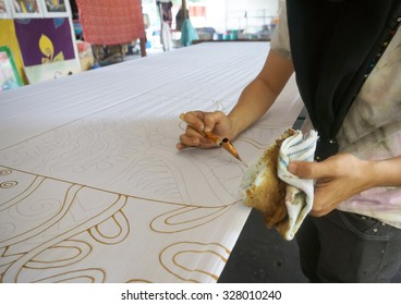 KUANTAN PAHANG, MALAYSIA - OCT 13 2015 : Unidentified local woman sketching freehand with canting tools and hot wax to create a traditional Batik Canting at workshop in Kuantan, Pahang Malaysia