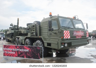 """KUBINKA, MOSCOW OBLAST, RUSSIA - Aug 24, 2017: Russian truck tractor BAZ-6403 with semi-trailer and t-80U tank, in the Park """"Patriot"""", international military-technical forum ARMY-2017, front view"""