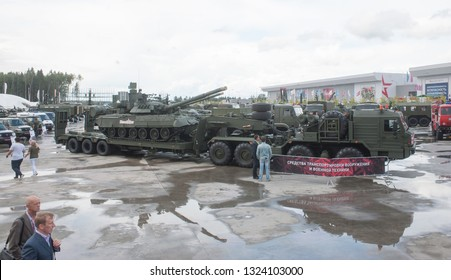 """KUBINKA, MOSCOW OBLAST, RUSSIA - Aug 24, 2017: Russian truck tractor BAZ-6403 with semi-trailer and T-80U tank, in the Park """"Patriot"""", international military-technical forum ARMY-2017, left view"""