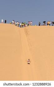 Kubuqi Desert, Inner Mongolia province / China - July 31st 2016: People sand dune sledging in Kubuqi desert in North China. Sand dune sledging is a popular tourist activity in Kubuqi desert.
