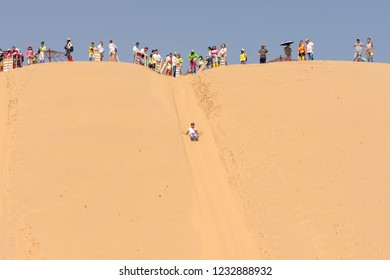 Kubuqi Desert, Inner Mongolia province / China - July 31st 2016: People sand dune sledging in Kubuqi desert in North China. Sand dune sledging is a popular tourist activity in Kubuqi desert.