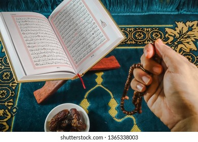Kuching, Malaysia - April 2019. An islamic concept for Ramadhan. Flat lay composition of zn open Qoran, Dates and a man's hand praying with tasbih (rosary beads) on his hand on top of a sajadah