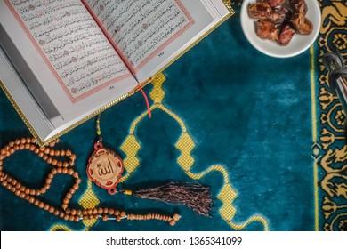Kuching, Malaysia - April 2019. An islamic concept for Ramadhan. Flat lay composition of an open Qoran, Dates and a tasbih (rosary beads) on top of a sajadah (praying mattress)