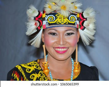 KUCHING, MALAYSIA - AUG 24, 2013: Beautiful Malaysian Dayak dancer wears traditional Kenyah Iban tribal costume during a Bornean folk festival and poses for the camera, on Aug 24, 2013.