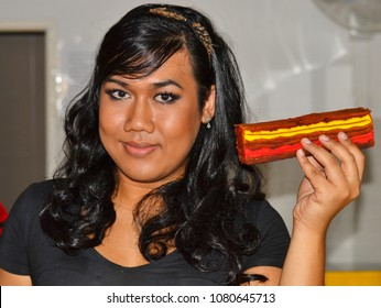 KUCHING, MALAYSIA - AUG 28, 2013: Young Malay genderqueer master baker with black curls poses for the camera with a piece of stripe cake (kek lapis), on Aug 28, 2013.