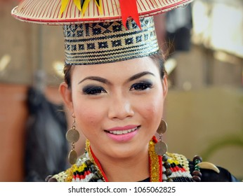 KUCHING, MALAYSIA - JULY 22, 2013: Young Malaysian Dayak woman from Borneo wears traditional Bidayuh attire with drop earrings made from silver coins and poses for the camera, on July 22, 2013.