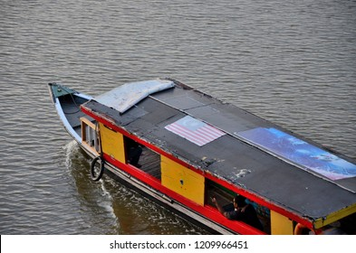 Kuching, Malaysia - October 10, 2018: A sampan river ferry boat cruise moves along the Sarawak River in East Malaysia. There is a Malaysia flag on the roof and a man with a child are seated in boat.