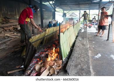 Kuching, Sarawak: June 24, 2017: A man attending his lemang cooking for Hari Raya Aidil Fitri. Lemang is a Malaysian traditional delicacy where glutinous rice.