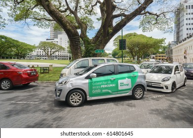 "Kuching Sarawak Malaysia - Apr 3, 2017 : Car with Grab advertisement words in Malay translated as ""Hi Kuching lets try for free today"". Grab offers ride-hailing through its app in Southeast Asia."