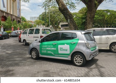 """Kuching Sarawak Malaysia - Apr 3, 2017 : Car with Grab advertisement words in Malay translated as """"Hi Kuching lets try for free today"""". Grab offers ride-hailing through its app in Southeast Asia."""