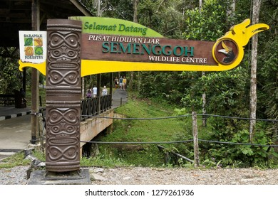 KUCHING, SARAWAK, MALAYSIA — APRIL 16, 2018. A sign marks the entrance to Semenggoh Wildlife Centre, set in a tropical forest, with visitors in the background.