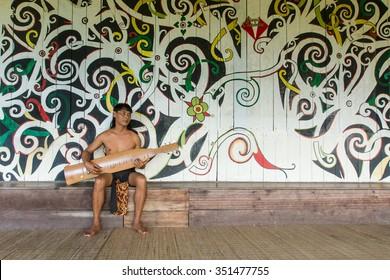 KUCHING, SARAWAK, MALAYSIA -December 14, 2015: Orang ulu (1 in 28 tribe of sarawak) people playing his Sape (Tradition music instrument) at Longhouse on Decemver 14, 2015 in Kuching, Sarawak, Malaysia