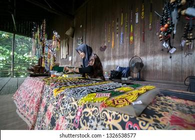 KUCHING, SARAWAK, MALAYSIA — JANUARY 6th, 2019.  A women make handmade beads to sell at visitors at Longhouse Sarawak Cultural Village, Kuching, Sarawak, Malaysia