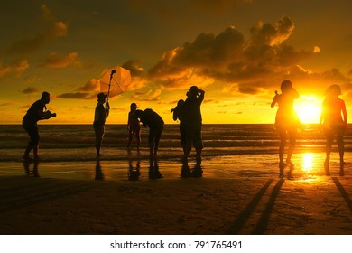 kuching sarawak,malaysia jan.8 2018 : photographer in action at the beach during burning twilight with sillhouette .there is a slightly noisy. focusing at the photographer.