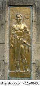 kuching, sarawak/malaysia - january  02, 1991: bronze  relief depicting an ethnical iban / dayak with parang wearing traditional clothes at the  charles brooke monument