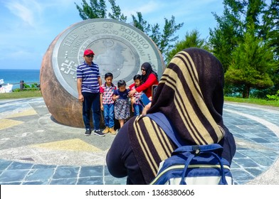 Kudat,Sabah-Feb 3,2018:Back view of muslim woman taking travel photo by smartphone of the people in the Tip of Borneo in Kudat,Sabah,Malaysia.