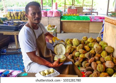 Kudat,Sabah-Feb 3,2018:Vendor of durians,often called the king of fruits peels fruits for sale in Kudat,Sabah,Malaysia.It is a big fruit with a strong smell & a hard shell with sharp thorns.