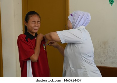 Kudat,Sabah-Malaysia,July 24,2019.A female student closed her eyes as a nurse injecting her for HPV immunisation, a must for female students.