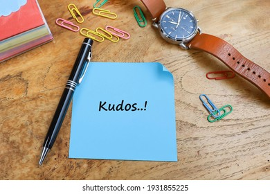 Kudos message written on the piece of paper, with a pen, paper clips, wristwatch and stacked of paper notes