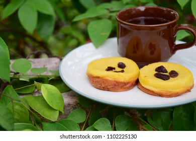 Kue Lumpur, Indonesian cuisine, made from potato, egg, coconut milk, butter, flour and sugar garnish with raisin. Served with cup of tea. Snack for breaking the fast or buka puasa