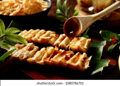 Kue Pancong. Traditional coconut cake from Betawi, Jakarta. The cake is being drizzled with palm sugar sauce.