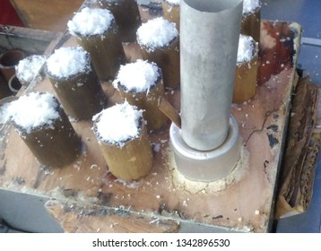 Kue putu or putu bambu. A traditional cylindrical-shaped steamed cake from Java, Indonesia, served with Java sugar and grated coconut