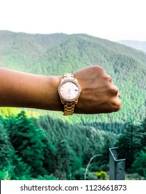 Kufri, Himachal Pradesh / India - 05/10/2018: A girl's hand showing her watch with lush green mountains in the background.