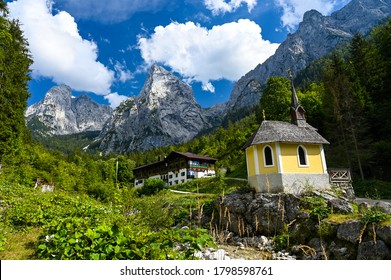 Kufstein, Austria / August 16, 2020: Fantastic view of a chapel and an alpine hut in the Kaiser valley surrounded by forest and the rough Kaiser Mountains.