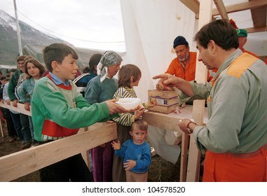 KUKES, ALBANIA, 18 APRIL 1999 - Italian aid workers feed  Kosovar Albanian refugees at a camp in northern Albania. Tens of thousands of ethnic Albanians have fled the troubled Yugoslavian province.