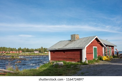 KUKKOLA, SWEDEN - AUGUST 8, 2018: Tourist explores fishermans cottages and sheds on the Swedish side of Torne river. Kukkola rapids has been a fishing site since medieval times.