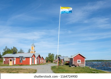 KUKKOLA, SWEDEN - AUGUST 8, 2018: Fishermans cottages and Torne valley flag on the Swedish side of Torne river. Kukkola rapids has been a fishing site since medieval times.