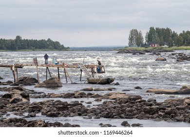 KUKKOLA, SWEDEN - AUGUST 9, 2018: Fishermen on the bridge at Kukkola rapids on the Swedish side of the border between Sweden and Finland. Kukkola rapids has been a fishing site since medieval times.