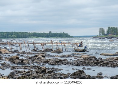 KUKKOLA, SWEDEN - AUGUST 9, 2018: Fishermen at Kukkola rapids on the Swedish side of the border between Sweden and Finland. Kukkola rapids has been a fishing site since medieval times.