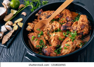 Kuku Paka, Kenyan chargrilled Chicken stewed in creamy spicy Coconut Sauce served in earthenware saucepan on a wooden table. ingredients on a stone cutting board, view from above, close-up