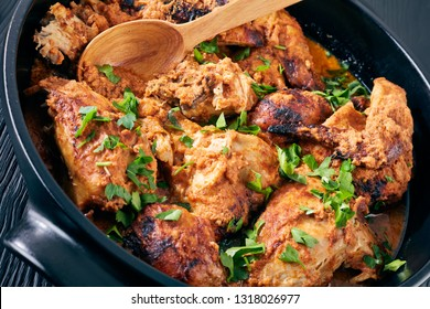Kuku Paka, Kenyan chargrilled Chicken stewed in creamy spicy Coconut Sauce in a earthenware saucepan on a black wooden table, view from above, close-up