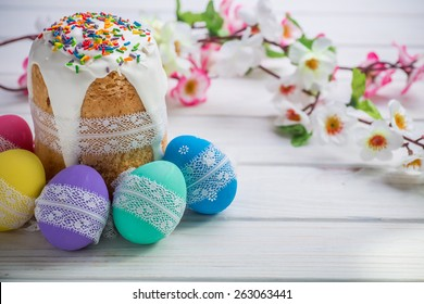 Kulich, traditional Russian Ukrainian Easter cake with icing and colored eggs with lace ribbon on white wooden background with flowers