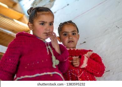 Kullu, Himachal Pradesh, India - April 01, 2019 : Portrait of twins himachali girl near her house on the street in Himalayan village in india